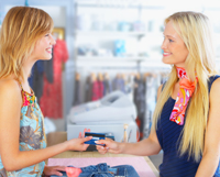 855324-a-buyer-and-a-shop-assistant-looking-at-each-other-with-smiles-by-the-pay-desk-in-the-clothing-department